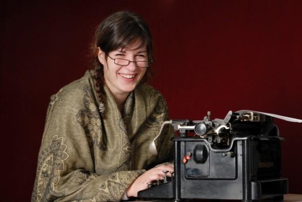 laughing woman typing on typewriter