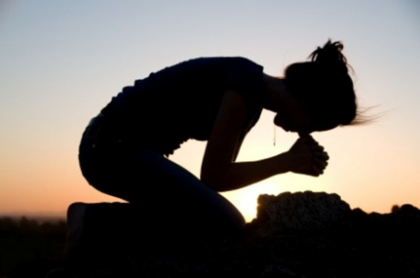 Woman on her knees praying