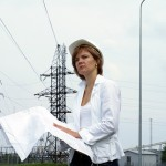 Woman engineer or architect with white safety hat drawings and electrical towers structure on background