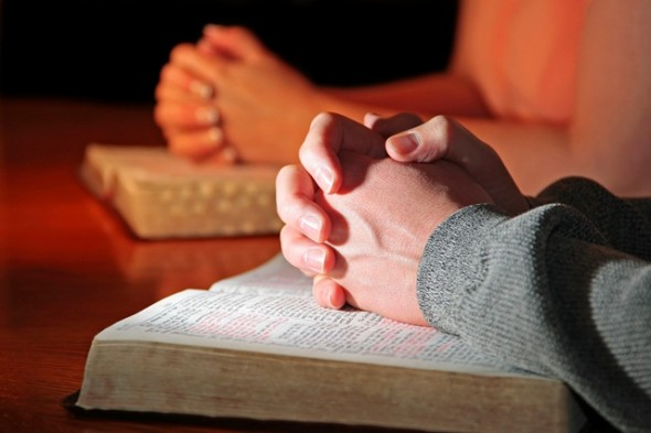 Couple praying with bible