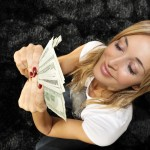 Woman with handful of money, looking pleased with herself
