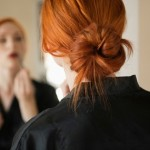woman in mirror applying makeup