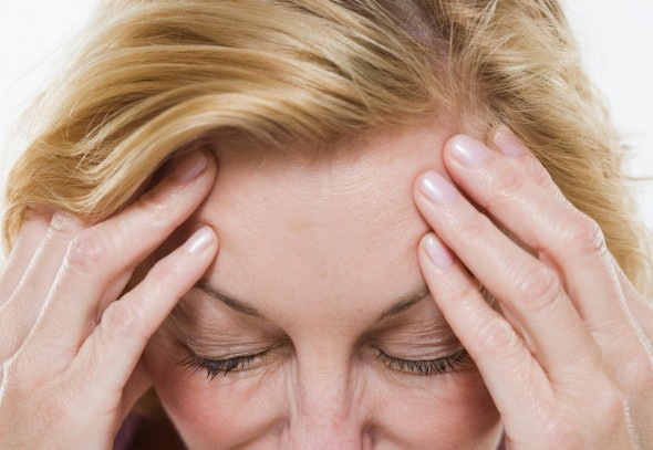 woman suffering from pain holding head